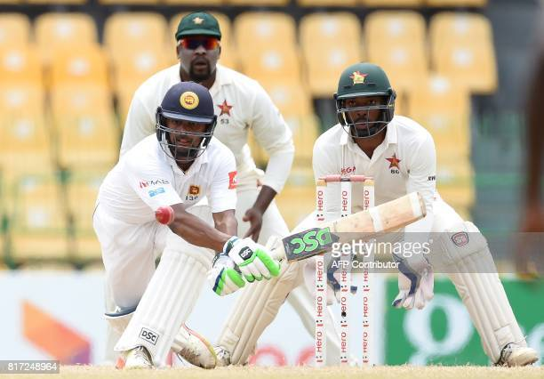Sri Lankan cricketer Asela Gunaratne plays a shot as as Zimbabwe wicketkeeper Regis Chakabva looks on during the final day of a oneoff Test match...