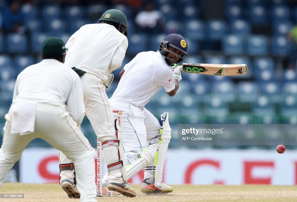 Sri Lankan cricketer Asela Gunaratne (R) plays a shot as as Zimbabwe wicketkeeper Regis Chakabva (C) looks on during the final day of a one-off Test match between Sri Lanka and Zimbabwe at the R Premadasa Cricket Stadium in Colombo on July 18, 2017. /