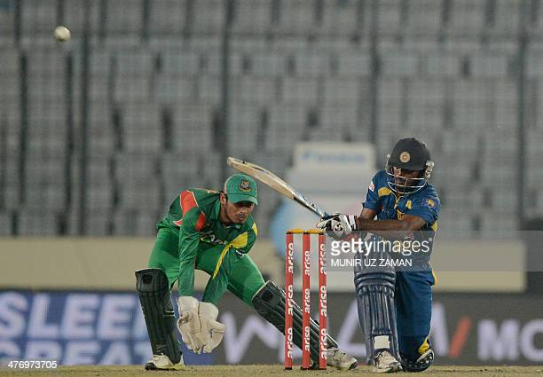 Sri Lankan cricketer Chaturanga de Silva plays a shot as Bangladesh wicketkeeper Anamul Haque looks on during the tenth match of the Asia Cup oneday...