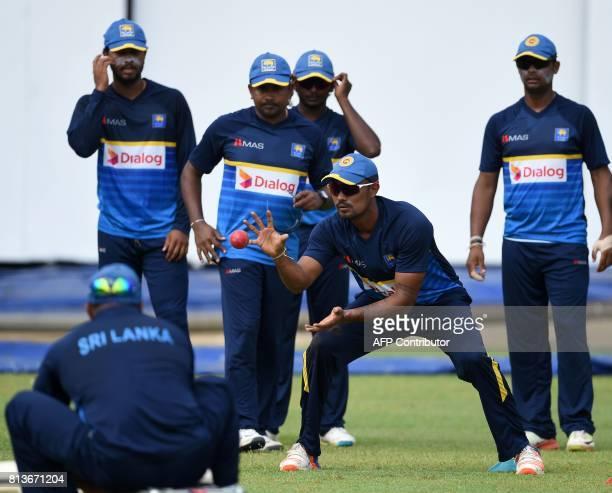 Sri Lankan cricketer Danushka Gunathilaka catches the ball as teammates looks on during a practice session at the R Premadasa Cricket Stadium in...