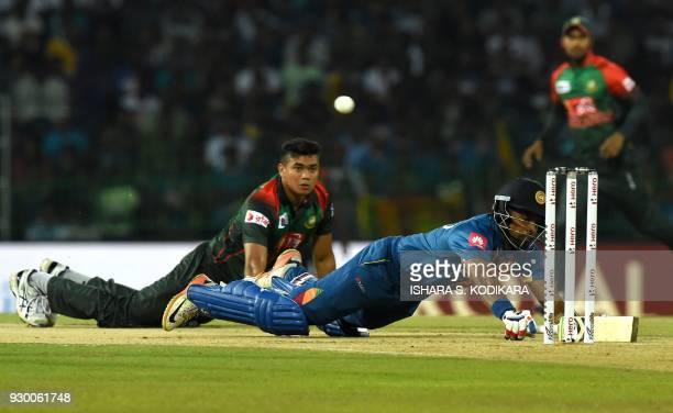 Sri Lankan cricketer Danushka Gunathilaka dives into his crease to complete a run as Bangladesh cricketer Taskin Ahmed looks on during the third...