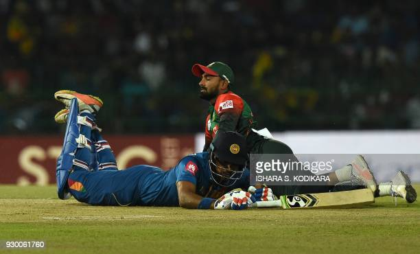 Sri Lankan cricketer Danushka Gunathilaka dives into his crease to complete a run as Bangladesh cricketer Tamim Iqbal looks on during the third...