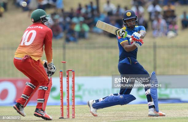 Sri Lankan cricketer Danushka Gunathilaka gets dismissed by Zimbabwe cricketer Malcolm Waller as wicketkeeper Peter Moor looks on during the fourth...