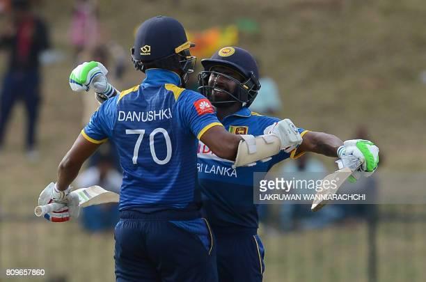 Sri Lankan cricketer Danushka Gunathilaka is congratulated by teammate Niroshan Dikwella after scoring a century during the third oneday...