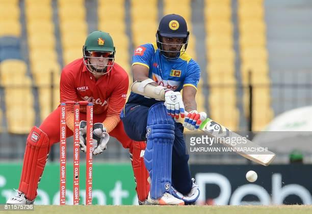 Sri Lankan cricketer Danushka Gunathilaka is watched by Zimbabwe wicketkeeper Peter Moor as he plays a shot during the fifth oneday international...