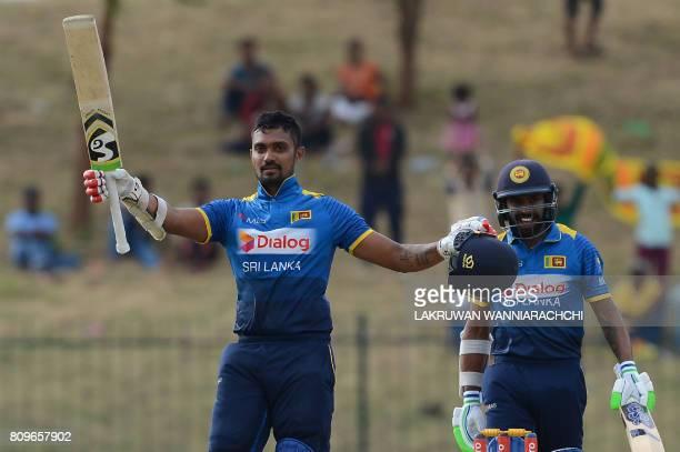 Sri Lankan cricketer Danushka Gunathilaka raises his bat and helmet in celebration after scoring a century during the third oneday international...