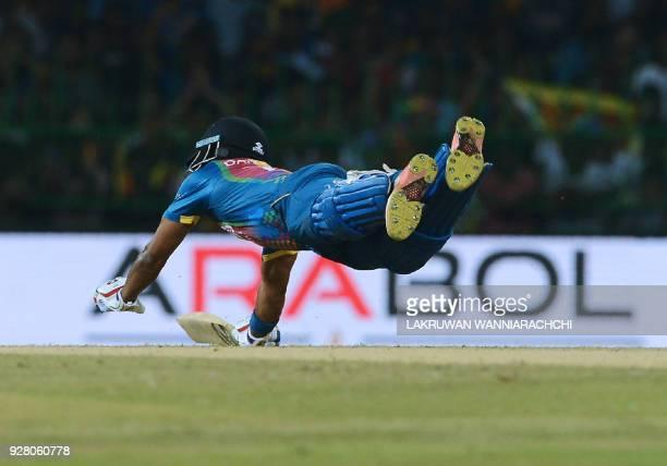 Sri Lankan cricketer Danushka Gunathilaka successfully dives and avoids being run out during the opening Twenty20 international cricket match between...