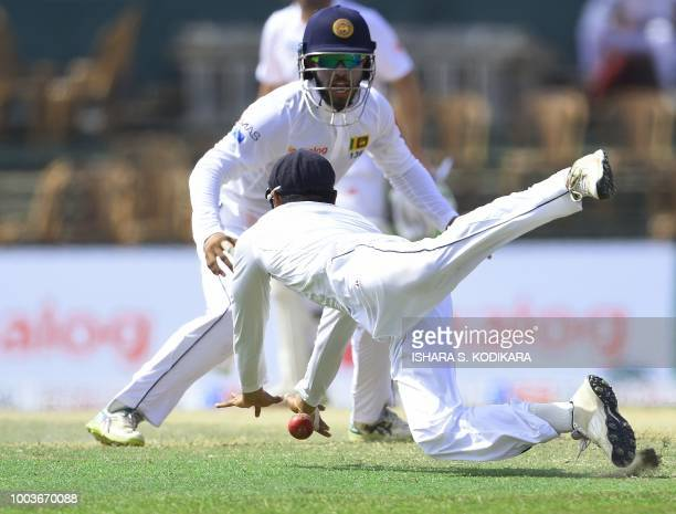 Sri Lankan cricketer Dhananjaya De Silva drops a catch of South African cricketer Theunis de Bruyn as Kusal Mendis looks on during the third day of...