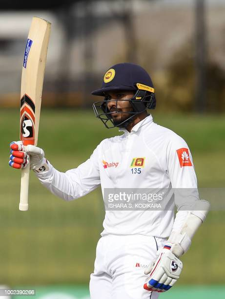 Sri Lankan cricketer Dhananjaya De Silva raises his bat to the crowd after scoring a halfcentury during the first day of the second Test match...