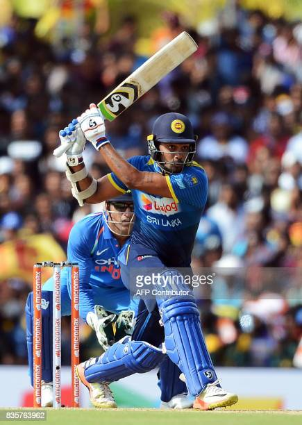 Sri Lankan cricketer Dhanushka Gunathilaka is watched by Indian wicketkeeper Mahendra Singh Dhoni as he plays a shot during the first One Day...