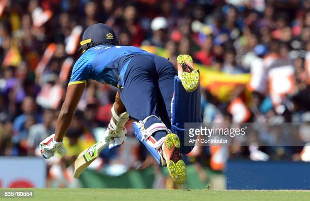 Sri Lankan cricketer Dhanushka Gunathilaka successfully dives and avoids being run out during the first One Day International cricket match between...