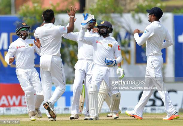 Sri Lankan cricketer Dilruwan Perera celebrates with his teammates after he dismissed South Africa's Dean Elgar during the second day of the opening...