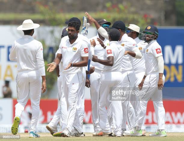 Sri Lankan cricketer Dilruwan Perera celebrates with team members during the 3rd day's play in the first Test cricket match between Sri Lanka and...