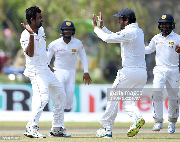 Sri Lankan cricketer Dilruwan Perera celebrates with teammates after he dismissed unseen Australian batsman Usman Khawaja during the second day of...