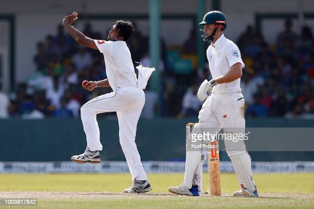 Sri Lankan cricketer Dilruwan Perera delivers a ball as South African cricketer Theunis de Bruyn looks on during the 3rd day's play in the 2nd test...