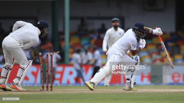Sri Lankan cricketer Dilruwan Perera is bowled out by Indian spin bowler Ravichandran Ashwin during the 3rd Day's play in the 2nd Test match between...