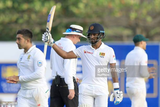Sri Lankan cricketer Dimuth Karunaratne celebrates after scoring 150 runs during the first day's play in the 1st Test cricket match between Sri Lanka...