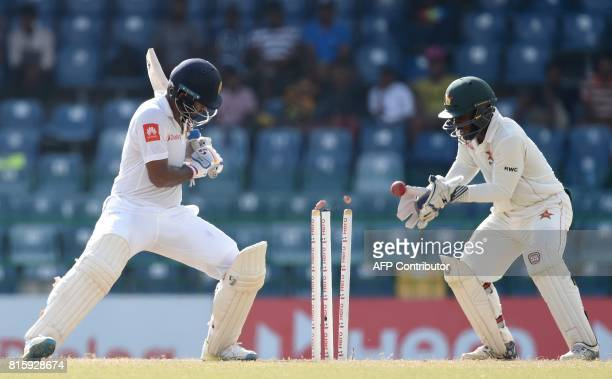 Sri Lankan cricketer Dimuth Karunaratne is dismissed by Zimbabwe cricketer Sean Williams during the fourth day of a oneoff Test match between Sri...