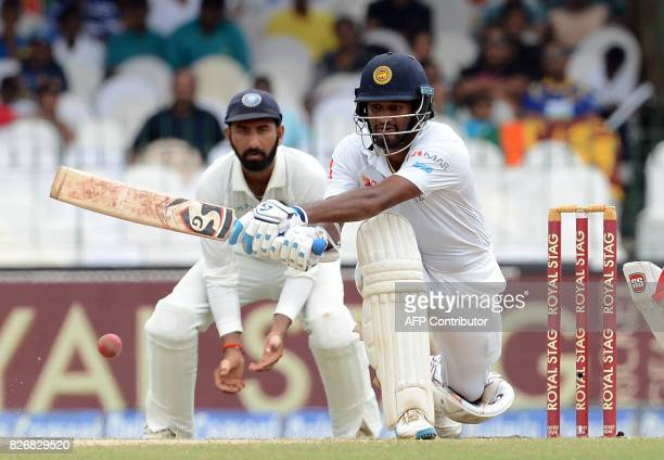 Sri Lankan cricketer Dimuth Karunaratne is watched by Indian cricketer Cheteshwar Pujara as he plays a shot during the fourth day of the second Test...