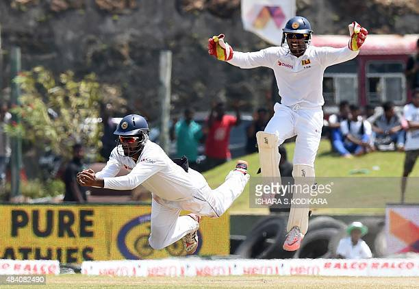 Sri Lankan cricketer Dimuth Karunaratne is watched by teammate Dinesh Chandimal as he takes a catch to dismiss unseen Indian batsman Amit Mishra...