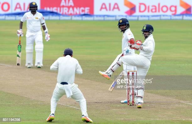 Sri Lankan cricketer Dimuth Karunaratne watches as Indian cricketer Ajinkya Rahane takes a catch to dismiss him as wicketkeeper Wriddhiman Saha looks...
