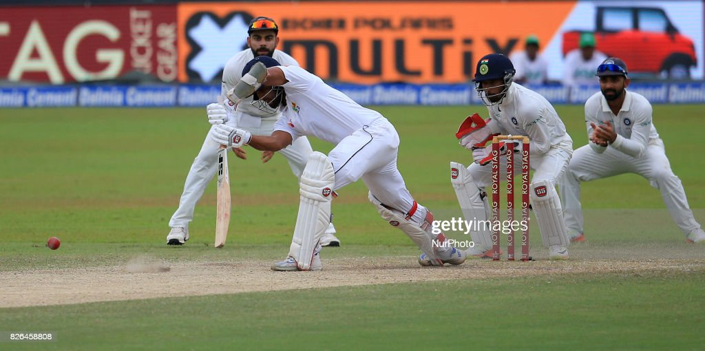 Sri Lankan cricketer Dinesh Chandimal plays a shot as indian cricket captain Virat Kohli(L) looks on during the 2nd Day's play in the 2nd Test match between Sri Lanka and India at the SSC international cricket stadium at the capital city of Colombo, Sri Lanka on Friday 04 August 2017.