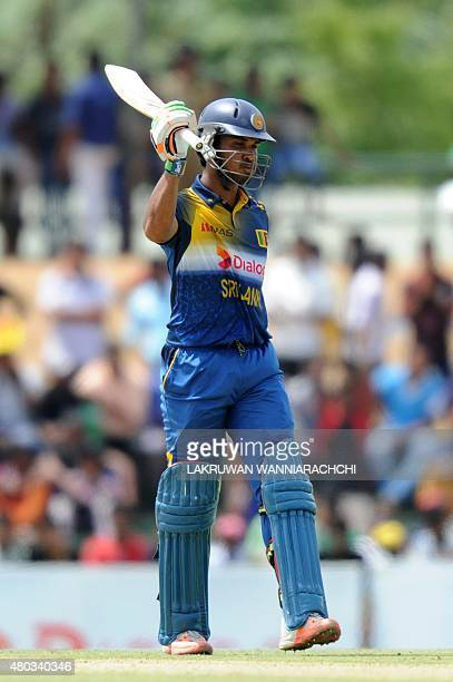 Sri Lankan cricketer Dinesh Chandimal raises his bat to the crowd after scoring a halfcentury during the first one day international cricket match...