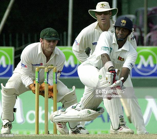 Sri Lankan cricketer Hashan Tillakaratne sweeps a ball as Australian wicketkeeper Adam Gilchrist and fielder Matthew Hayden look on during the third...