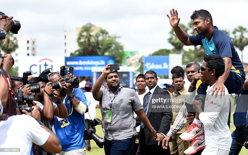 Sri Lankan cricketer Kumar Sangakkara (R) waves to the crowd as his teammates carry him around the pitch in a lap of honour at close of play of the fifth and final day of the second Test cricket match between Sri Lanka and India at the P. Sara Oval Cricket Stadium in Colombo on August 24, 2015. Sri Lanka's Kumar Sangakkara bid a tearful farewell to international cricket on August 24, 2015 and was immediately offered the post of the island's top envoy in Britain where he plays county cricket. AFP PHOTO / Ishara S. KODIKARA
