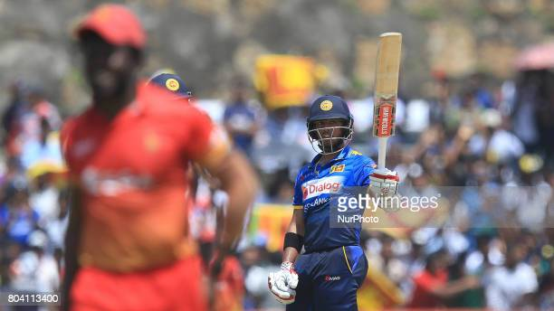 Sri Lankan cricketer Kusal Mendis acknowledges the crowd by raising his bat after scoring 50 runs during the 1st oneday international cricket match...