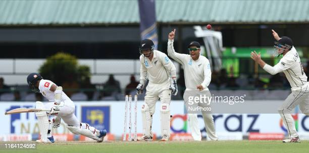 Sri Lankan cricketer Kusal Mendis is bowled out as New Zealand wicket keeper BJ Watling Ross Taylor and Tom Latham celebrate during the fifth and...