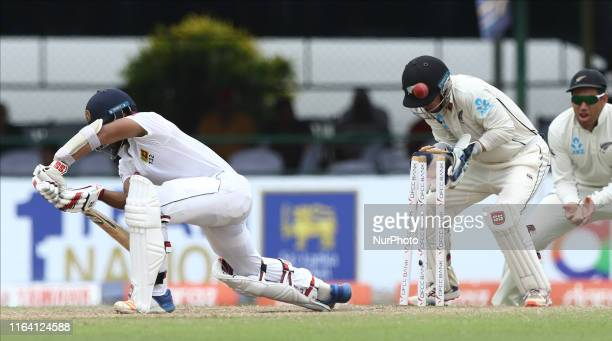 Sri Lankan cricketer Kusal Mendis is bowled out watched by New Zealand wicket keeper BJ Watling and Ross Taylor during the fifth and final day's play...