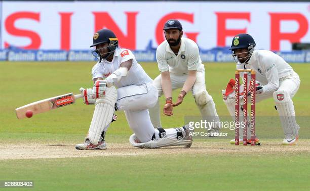 Sri Lankan cricketer Kusal Mendis is watched by Indian wicketkeeper Wriddhiman Saha and Cheteshwar Pujara as he plays a shot during the third day of...