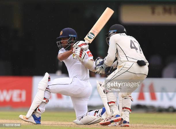 Sri Lankan cricketer Kusal Mendis plays a shot as New Zealand wicket keeper BJ Watling looks on during the first day's play of the second test...