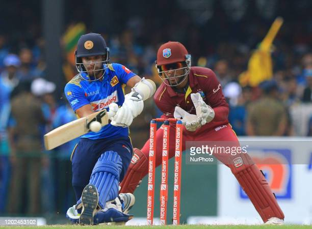 Sri Lankan cricketer Kusal Mendis plays a shot as West Indies wicket keeper Shai Hope looks on during the 1st One Day International cricket match...