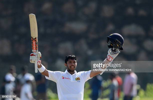 Sri Lankan cricketer Kusal Mendis raises his bat and helmet in celebration after scoring a century during the first day of the opening Test cricket...