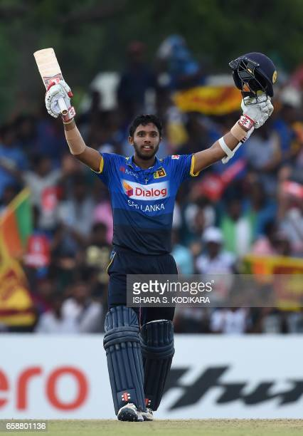 Sri Lankan cricketer Kusal Mendis raises his bat in celebration after scoring a century during the second one day international cricket match between...