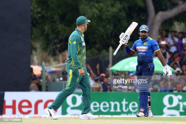 Sri Lankan cricketer Kusal Perera celebrates after scoring 50 runs as South African cricket captain Faf Du Plessis looks on during the 1st One Day...