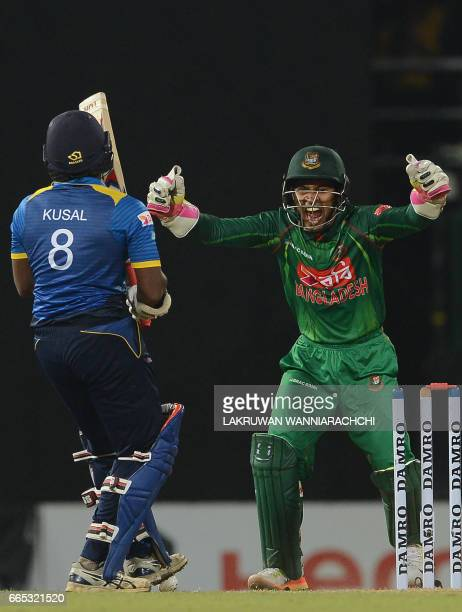 Sri Lankan cricketer Kusal Perera gets dismissed by Bangladesh cricketer Shakib Al Hasan as wicketkeeper Mushfiqur Rahim looks on during the second...