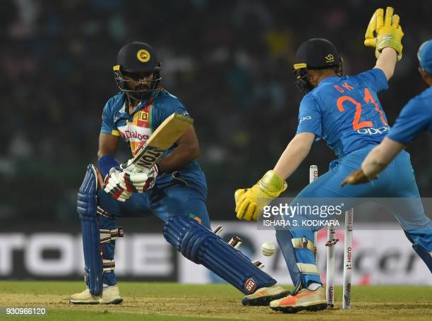 Sri Lankan cricketer Kusal Perera is dismissed by Indian cricketer Washington Sundar as Wicketkeeper Dinesh Karthik looks on during the fourth...