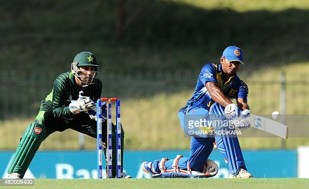 Sri Lankan cricketer Kusal Perera is watched by Pakistani wicketkeeper Sarfraz Ahmed as he plays a shot during the fifth and final one day...