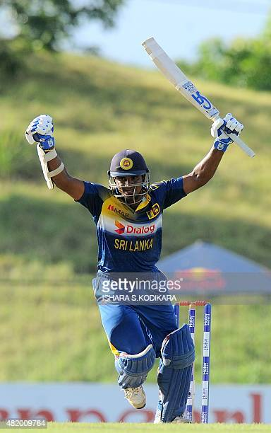 Sri Lankan cricketer Kusal Perera raises his bat in celebration after scoring a century during the fifth and final one day international cricket...