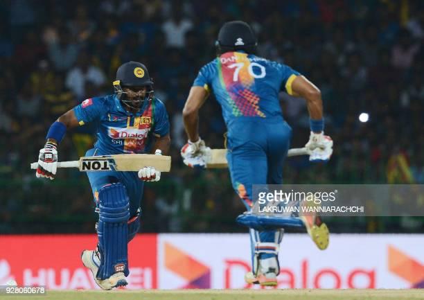 Sri Lankan cricketer Kusal Perera teammate Danushka Gunathilaka run between the wickets during the opening Twenty20 international cricket match...