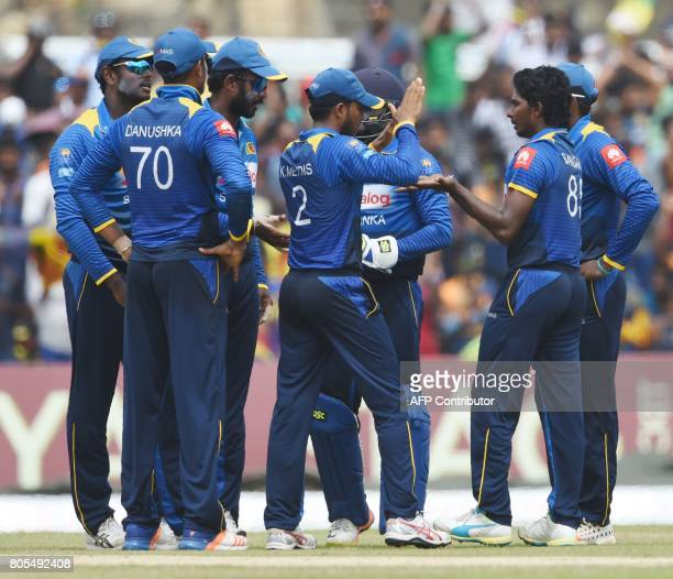 Sri Lankan cricketer Lakshan Sandakan celebrates with his teammates after he dismissed Zimbabwe cricketer Craig Ervine looks on during the second...
