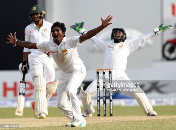 Sri Lankan cricketer Lakshan Sandakan celebrates with teammate wicketkeeper Niroshan Dickwella after he dismissed Bangladesh batsman Taijul Islam...