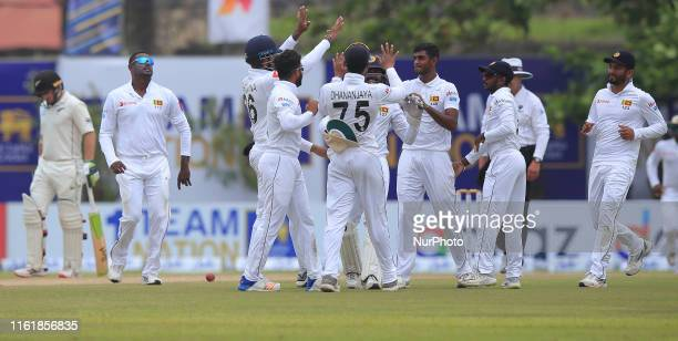 Sri Lankan cricketer Lasith Embuldeniya celebrates with teammates after taking the wicket of New Zealand cricketer Ross Taylor during the third day...
