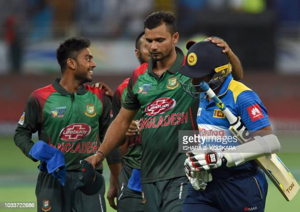 Sri Lankan cricketer Lasith Malinga and Bangladesh captain Mashrafe Mortaza leave the field after with Bangladesh players at the end of the one day...