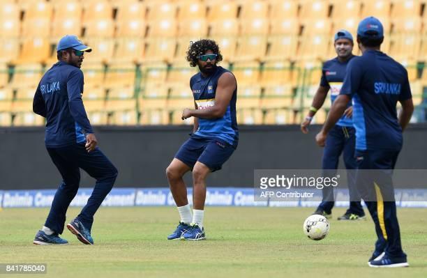 Sri Lankan cricketer Lasith Malinga and captain Upul Tharanga play football during a practice session at R Premadasa Stadium in Colombo on September...