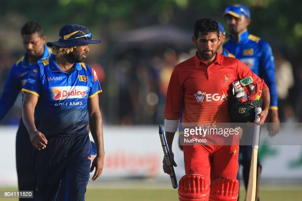 Sri Lankan cricketer Lasith Malinga and Zimbabwe's Sikandar Raza walks back to pavilion after Zimbabwe secured a historic win against Sri Lanka in...