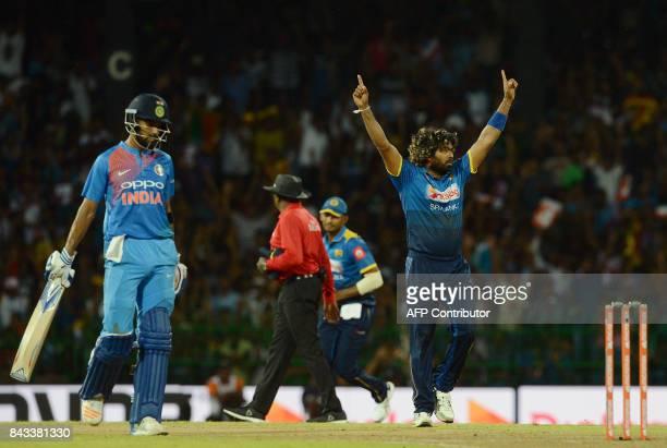 Sri Lankan cricketer Lasith Malinga celebrates after he dismissed Indian cricketer Rohit Sharma during the Twenty20 international cricket match...